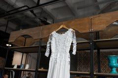 Деревенская белая смертная казнь через повешение платья свадьбы на кухонном шкафе loft стоковое фото