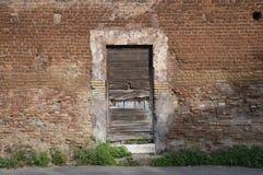 Деревенская дверь в древней стене Стоковые Изображения