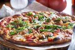 Деревенская древесина увольняла пицца с зажаренными в духовке чесноком и arugula Стоковая Фотография RF