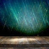 Деревенская деревянная таблица перед серебром яркого блеска, синью, и bokeh золота освещает Стоковое фото RF