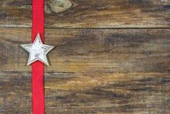 Деревенская звезда рождества на деревянной доске с красной лентой Стоковые Фото