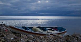 Деревенская рыбацкая лодка в береге реки на заходе солнца Стоковые Изображения RF