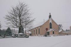 Деревенская церковь предусматриванная в снеге во время шторма Эммы, также известного как зверь от востока, при вороны летая прочь Стоковое Фото