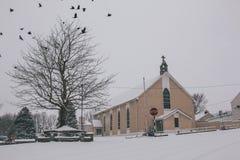 Деревенская церковь предусматриванная в снеге во время шторма Эммы, также известного как зверь от востока, при вороны летая прочь Стоковая Фотография