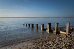 Деревенские деревянные столбы в море стоковые изображения rf