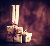 Деревенские ретро подарки, присутствующие коробки на деревянной предпосылке время конца рождества предпосылки красное вверх Стоковая Фотография
