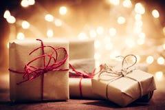 Деревенские ретро подарки, присутствующие коробки на предпосылке яркого блеска время конца рождества предпосылки красное вверх Стоковое Фото