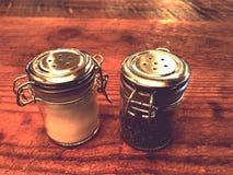 Деревенские шейкеры соли и перца на деревянном столе Стоковая Фотография