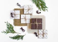 Деревенские handmade подарочные коробки на белой предпосылке украшенной с ветвями Взгляд сверху, плоское положение Стоковые Фотографии RF