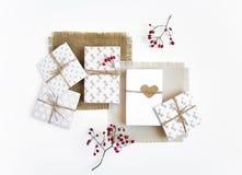 Деревенские handmade подарочные коробки на белой предпосылке украшенной с ягодами Взгляд сверху, плоское положение Стоковые Изображения RF