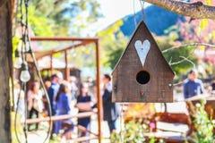 Деревенский деревянный Birdhouse в переднем плане и приглушенные люди в Backgr Стоковые Изображения RF