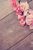 Деревенский деревянный стол с розовыми розами и лепестками розы Стоковое фото RF