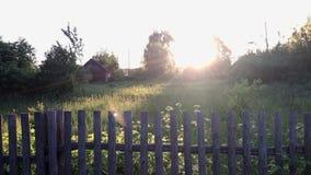 Деревенский ландшафт в заднем солнечном свете Старая деревянная загородка, и позади оно лужайка видеоматериал