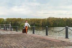 Деревенский мальчик идет пристань с огромным ретро старым чемоданом стоковые изображения