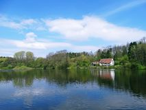 Деревенский дом на озере в лесе Стоковые Фотографии RF