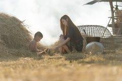 Деревенский парень уча с его сестрой на соломе Стоковое Изображение