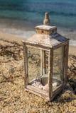 Деревенский фонарик с свечой и seashells взморьем Стоковое Изображение