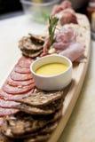 Деревенское представление доски мясной закуски отрезанного и вылеченного m Стоковые Фотографии RF