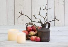 Деревенское decoraton с яблоками, свечами и хворостинами в вазе на белой деревянной предпосылке стоковые изображения rf