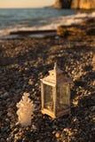 Деревенское lattern и коралл сформировали свечу на Pebble Beach Стоковая Фотография RF