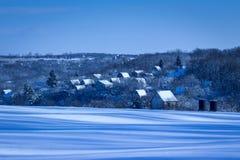 Деревня зимы за снежным полем на красивом вечере зимы Стоковые Фото