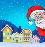 Деревня зимы с скрываясь Санта Клаусом Стоковое Фото