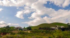 Деревня на заднем плане зеленых холмов Стоковые Фото