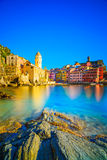 Деревня, церковь, утесы и море Vernazza затаивают на заходе солнца Cinque Стоковое фото RF