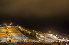 Деревня лыжи на ноче с наклоном освещает, место для стоянки, автомобили, строение Стоковые Фото