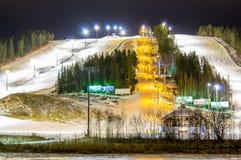 Деревня лыжи на ноче с наклоном освещает, место для стоянки, автомобили, строение Стоковое фото RF