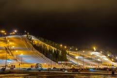 Деревня лыжи на ноче с наклоном освещает, место для стоянки, автомобили, строение Стоковая Фотография RF