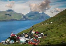 Деревня Kunoy с красной церковью с океаном в backgroud и clloudy небе стоковое фото rf