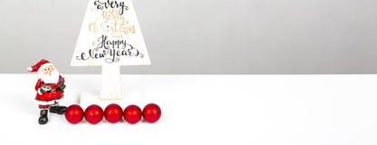 Дерево красивого минимального рождества деревянное при веселое Christmass и счастливый Новый Год написанные, с малым Санта Клаусо стоковые изображения