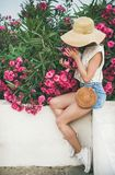 Дерево олеандра молодой белокурой женщины пахнуть зацветая Стоковые Фото