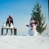 Дерево снеговика и xmas на снежном ландшафте стоковое фото