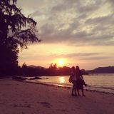 Деревья облака природы моря песка пляжа влюбленности мальчика девушки любовников захода солнца Таиланда KoPhangan стоковое фото