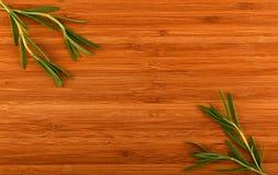 Деревянная бамбуковая разделочная доска с листьями розмаринового масла Стоковое фото RF
