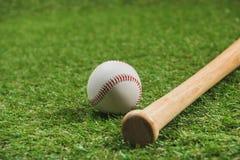 Деревянная бейсбольная бита с шариком на зеленой траве Стоковые Фотографии RF