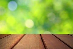 Деревянная верхняя часть пола на зеленой предпосылке bokeh Стоковая Фотография