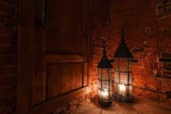 Деревянная дверь в комнате кирпича с свечами Зима приходит Стоковое фото RF