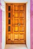 Деревянная дверь на розовой стене Стоковое Фото