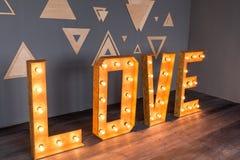 Деревянная влюбленность литерности с электрическими лампочками Стоковые Фотографии RF
