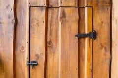 Деревянная дверь украшенная с защелкой и шарниром металла стоковые фотографии rf
