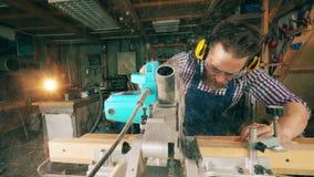 Деревянная доска получает отрезанной механически мужским работником Мастер работая в плотничестве сток-видео