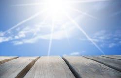 Деревянная доска с солнечным голубым небом как предпосылка стоковое фото rf