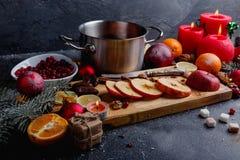Деревянная доска с яблоками, кастрюлькой, плитой с клюквами и несколькими красных свечей Взгляд со стороны Стоковое Изображение RF