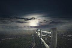 Деревянная загородка с туманом на пугающем поле травы на ноче Стоковые Фото