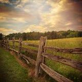 Деревянная загородка с облаками в предпосылке страны Стоковая Фотография