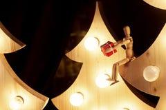 Деревянная игрушка давая подарочную коробку сидя на рождественской елке с ретро Стоковое Изображение