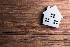 Деревянная игрушка дома на деревянной предпосылке с космосом экземпляра Реальное Estat Стоковое Изображение